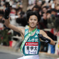 Aoyama Gakuin's Keigo Yuhara breaks the tape to win the Hakone ekiden in Otemachi on Friday. | KYODO