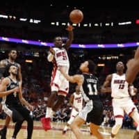 The Heat's Kendrick Nunn leaps to make a pass over the Spurs' Bryn Forbes in the second half on Wednesday in Miami. | AP