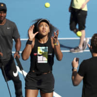 Naomi Osaka warms up during a practice session on Sunday in Melbourne, Australia. Osaka will begin the defense of her Australian Open title on Monday against Marie Bouzkova. | AP