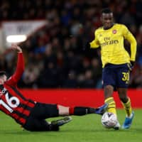 Arsenal's Eddie Nketiah and Bournemouth's Lewis Cook vie for the ball in an F.A. Cup match on Monday in Bournemouth, England. | REUTERS