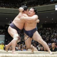 Myogiryu (left) pushes yokozuna Kakuryu toward the edge of the ring during the fourth day of the New Year Grand Sumo Tournament on Wednesday at Ryogoku Kokugikan. | KYODO