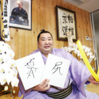 Tokushoryu holds up signboards spelling out makujiri, which means lowest ranking in the makuuchi division, during a news conference on Monday in Tokyo. On Sunday, Tokushoryu became the first wrestler in 20 years to win an Emperor's Cup from that position. | KYODO