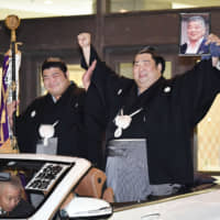 New Year Grand Sumo Tournament champion Tokushoryu (right) holds up a portrait of his deceased university sumo coach, Katsuhito Ito, on Sunday at Ryogoku Kokugikan. | KYODO