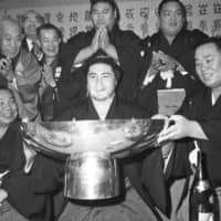 Taiho, holding a ceremonial cup in January 1971, became one of the greatest wrestlers in sumo history. He's second on the all-time list of tournament title winners with 32. | KYODO
