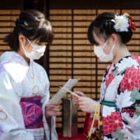 Women in kimono wear face masks to help prevent the spread of the SARS-like Wuhan coronavirus as they read their fortunes at Sensoji Temple in Tokyo on Monday. | AFP-JIJI