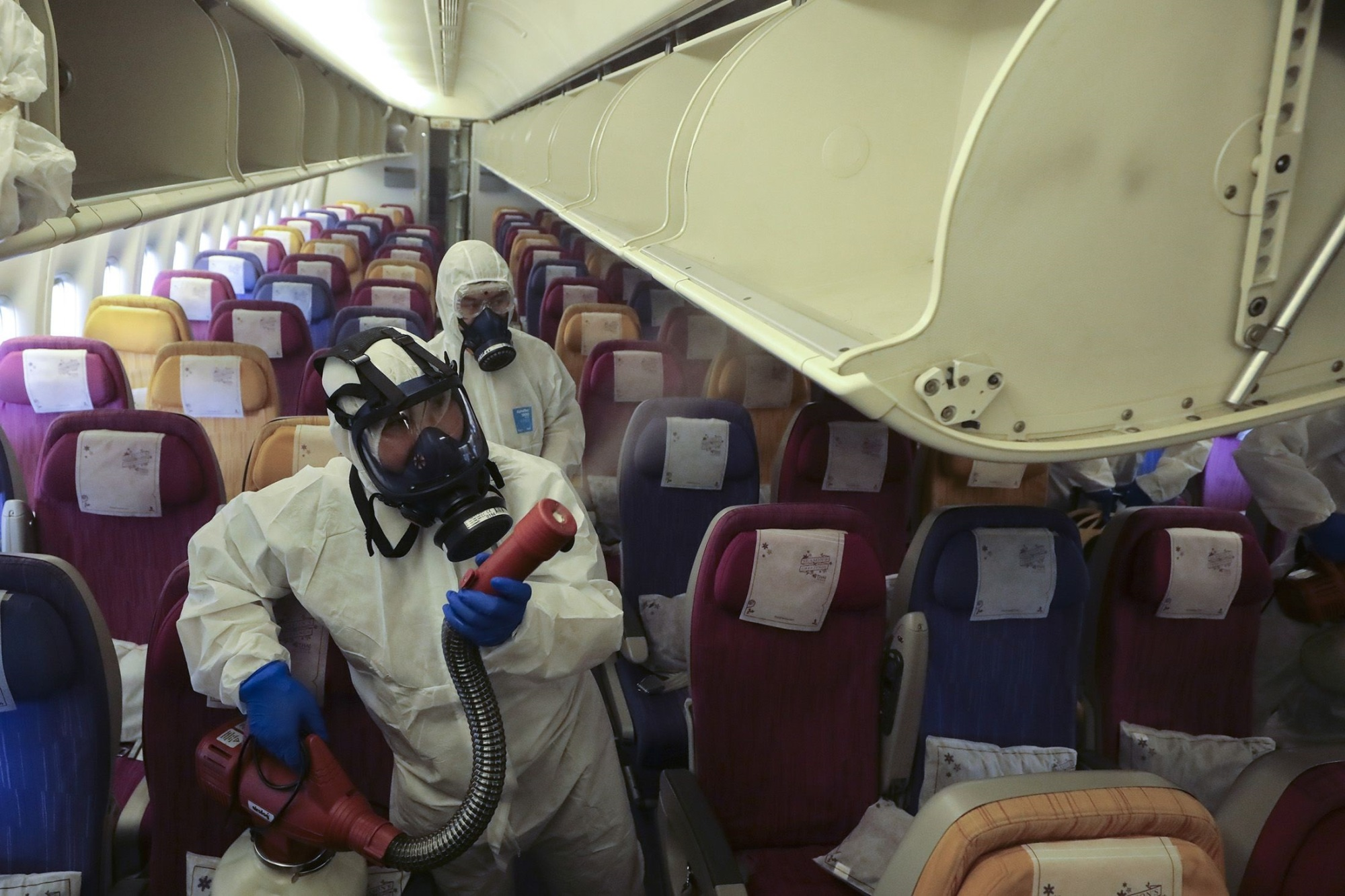 Disinfectant is sprayed on an airplane by staff in hazmat suits. | PHOTOGRAPHER: PATIPAT JANTHONG/B