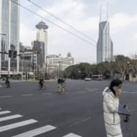 Only a few people in Shanghai are using the normally bustling Nanjing Road last Wednesday. | BLOOMBERG