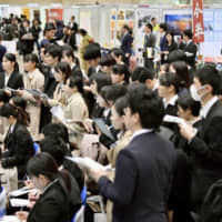 Students attend a job seminar at a convention center in Chiba in March last year. | KYODO