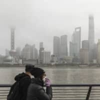 A couple walk in Shanghai on Friday. Broad policy direction for the world's central banks will hinge on how the Chinese government responds to the coronavirus outbreak. | BLOOMBERG