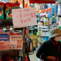 A sign announces that masks are sold out at a grocery store following the outbreak of a new coronavirus, in Hong Kong Sunday. | REUTERS