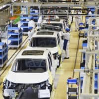Workers assemble cars at Honda Motor Co.'s plant in coronavirus-hit Wuhan, China, in April last year. | KYODO
