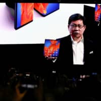 Richard Yu, CEO of Huawei Technologies Consumer Business Group, holds a Huawei Mate Xs foldable smartphone as he talks to the audience on a big screen during a Huawei stream product launch event in Barcelona, Spain, Monday. | REUTERS