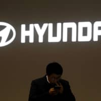 A man walks past the logo of Hyundai Motor during the 2019 Seoul Motor Show in Goyang, South Korea, last March. | REUTERS