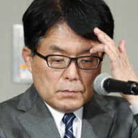 Japan Post Holdings Co. President Hiroya Masuda faces the media during a news conference Friday in Tokyo over the discovery of more improper insurance sales. | KYODO