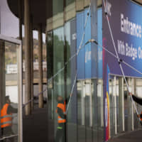Workers clean the windows in one of the entrances at the Mobile World Congress 2020 venue in Barcelona, Spain, Tuesday. Organizers of the world's biggest mobile technology fair are pulling the plug over worries about the viral outbreak from China. | AP