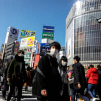 People wearing masks cross the famous scramble crossing in Tokyo's bustling Shibuya district. | REUTERS