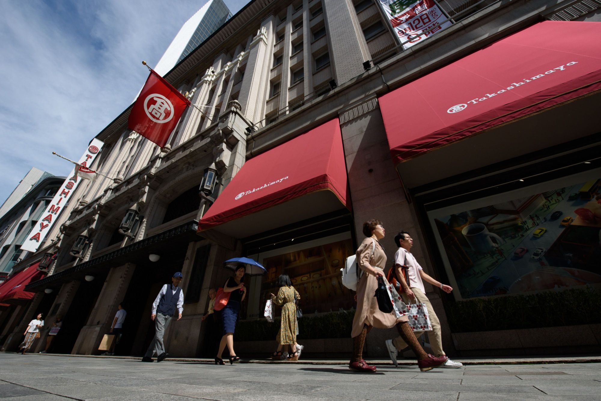 Pedestrians walk past a department store operated by Takashimaya Co. in Nihonbashi district of Tokyo in September 2018. Major department stores reported drops in Lunar New Year sales this year in the wake of the coronavirus outbreak in China. | BLOOMBERG