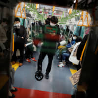 Passengers wear masks on a train in Tokyo last week. | REUTERS