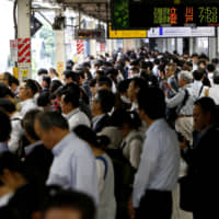 Passengers wait for a train in Kawasaki in June 2017. | REUTERS