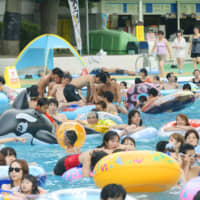 A swimming pool at the Toshimaen amusement park in Nerima Ward, Tokyo, draws big crowds during the summer. | KYODO