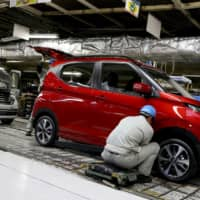 A man works on a car at Mitsubishi Motors Corp.'s Mizushima plant in Okayama Prefecture. Japan's factory activity suffered its steepest contraction in seven years in February following outbreaks of new coronavirus COVID-19, which originated in central China. | BLOOMBERG