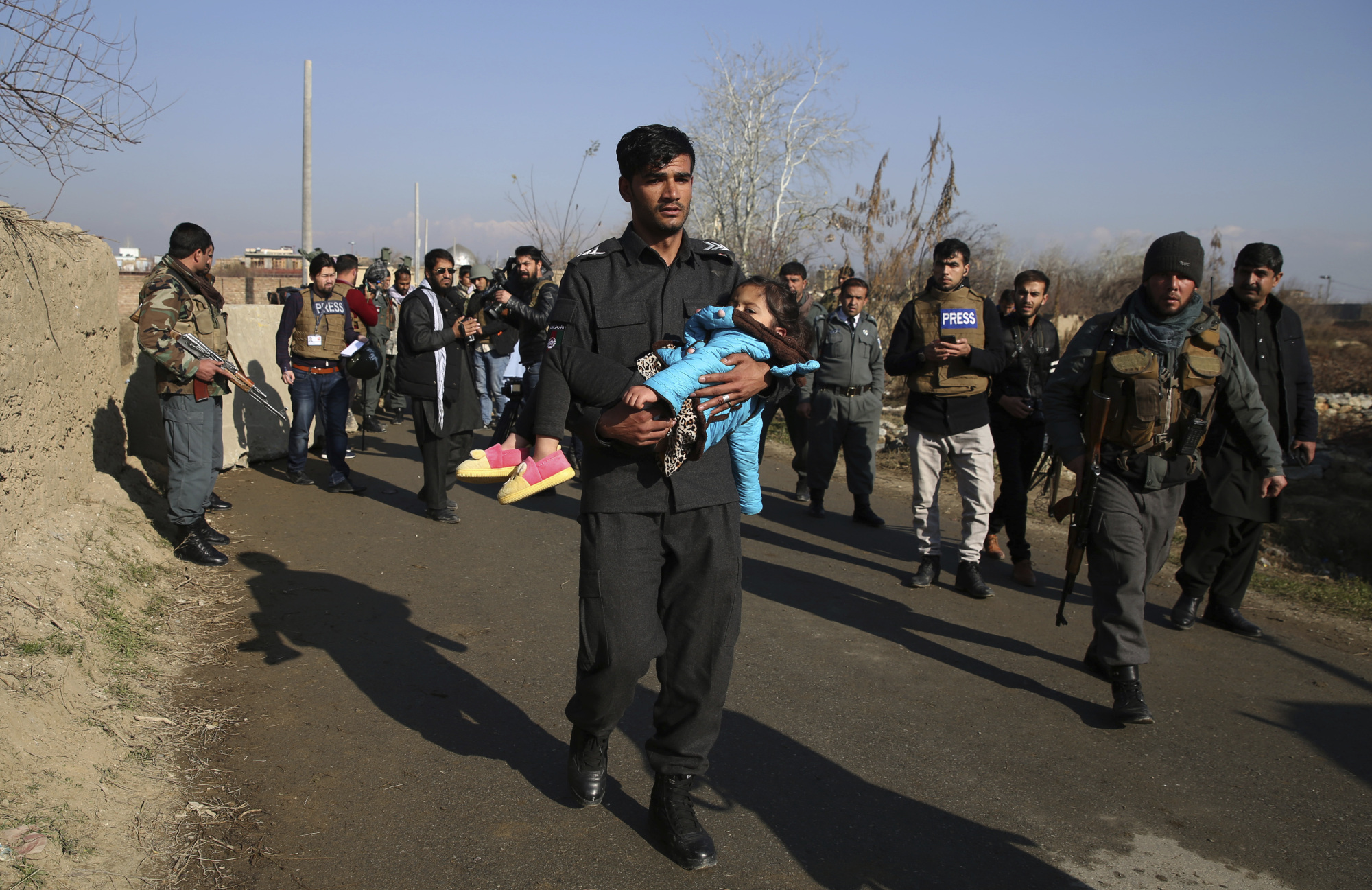 An Afghan security policeman carries his injured daughter after an attack near Bagram Air Base In Parwan province on Dec. 11. | AP