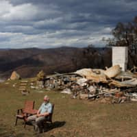 Donald Graham, 68, sits for an interview beside his burned home in Buchan, Victoria, Australia, on Jan. 23. | REUTERS