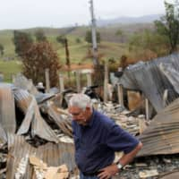 An Australian farmer in front of his burned home in Buchan, Victoria state, on Jan. 23. | REUTERS