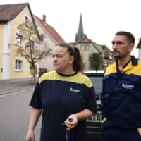 Kristin and Thomas Schmitt, employees of the Bamberg branch of the French tire manufacturer Michelin, leave their house in Baunach on Feb. 13. | REUTERS