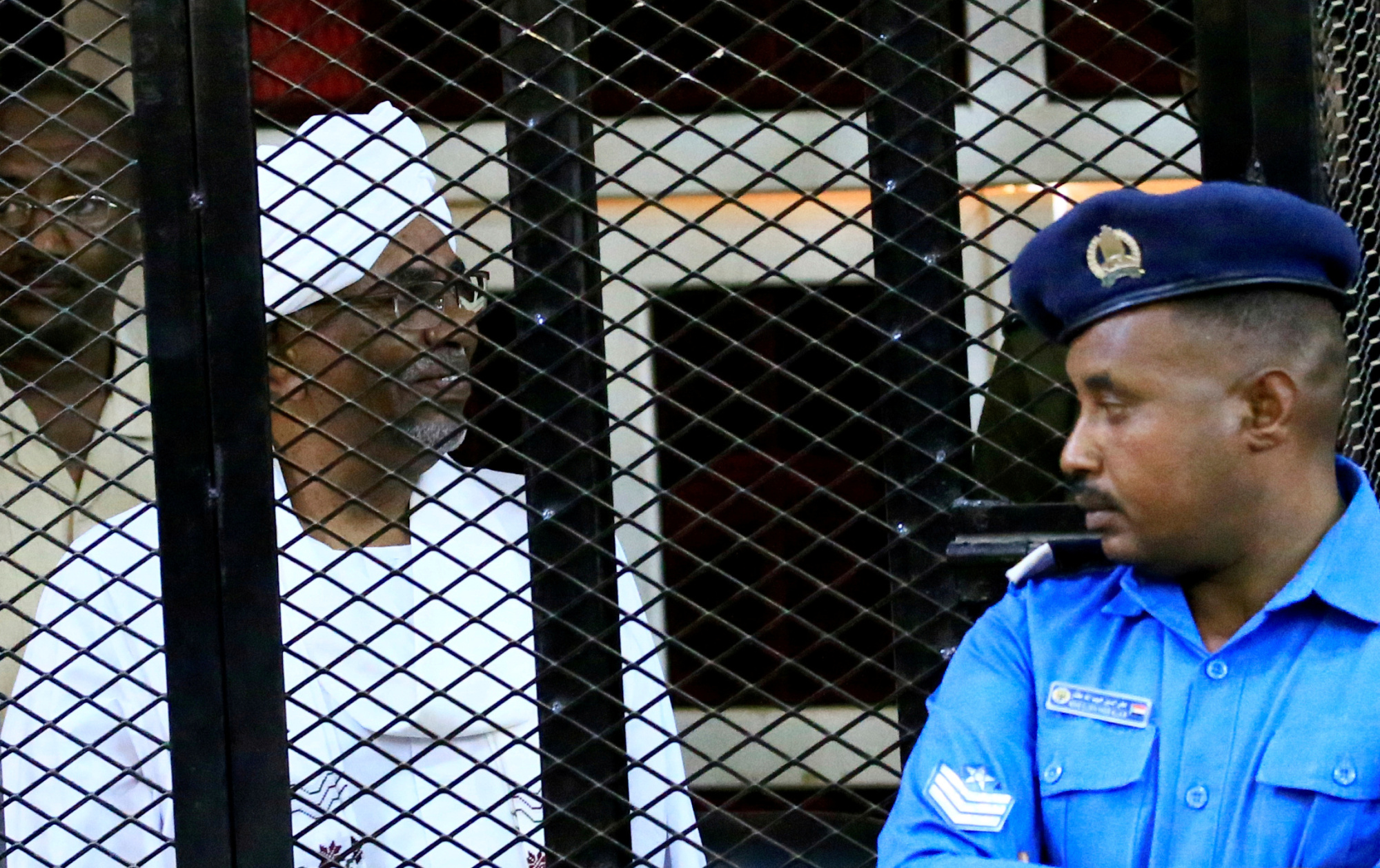 Sudan's jailed former president, Omar Hassan al-Bashir, sits inside a cage during a court hearing in Khartoum in December.   REUTERS