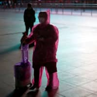 A woman wears a face mask and plastic raincoat as a protection from coronavirus at Shanghai railway station, in Shanghai Monday. | REUTERS