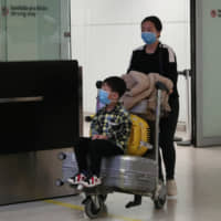 Travelers, wearing masks as a precautionary measure to avoid contracting coronavirus, are seen at Guarulhos International Airport in Guarulhos, Sao Paulo state, Brazil, Monday.   REUTERS