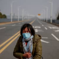 A mother reacts as she pleads with police to let her daughter pass a checkpoint for cancer treatment Saturday after she arrived from Hubei province at the Jiujiang Yangtze River Bridge in Jiujiang, China, as the country deals with the outbreak of a new coronavirus. | REUTERS