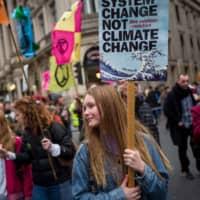 Climate activists march during a protest organized by the climate change action group Extinction Rebellion in London on Saturday. The youth-led Teach the Future campaign network in Britain is demanding a new U.K. law that would instruct all schools to teach climate issues. | AFP-JIJI