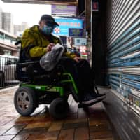 A patient stops in front of a shuttered Hong Kong pharmacy on Feb. 13. | AFP-JIJI