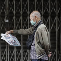 A man wearing a protective mask reads a Chinese language newspaper that says 'Philippines bans travelers from China, Hong Kong and Macau' as he walks at Manila's Chinatown on Monday. Philippine President Rodrigo Duterte has approved a temporary ban on all travelers, except Filipinos, from China and its autonomous regions. | AP