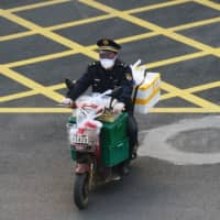 A man wearing a face mask rides a bike filled with food supplies in Wuhan, the epicenter of the novel coronavirus outbreak, in China's Hubei province Monday. | REUTERS