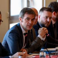French Health Minister Olivier Veran (center) takes part in a meeting on the COVID-19 outbreak at the Health Ministry on Tuesday in Paris. On Saturday, he criticized dependence on Chinese supplies for multiple industries. | AFP-JIJI