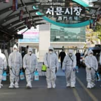 Workers spray disinfectant at a market in the South Korean city of Daegu on Sunday amid an outbreak of COVID-19. | AFP-JIJI