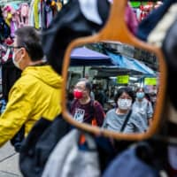 People wearing protective face masks walk through a market in Hong Kong on Tuesday. | AFP-JIJI