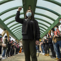 Winnie Yu, chairwoman of the Hospital Authority Employees Alliance, leads a protest demanding the government shut all entry points from China amid the deadly new virus outbreak outside Queen Mary Hospital in Hong Kong on Monday. | BLOOMBERG