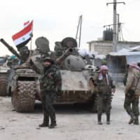 Syrian government forces deploy near the Damascus-Aleppo highway in the southern part of Syria's northern Aleppo province on Monday. Syrian regime artillery killed five Turkish soldiers in Idlib Monday, Turkey's defense ministry said, as the number of people displaced by violence in the region neared 700,000 since December. | AFP-JIJI