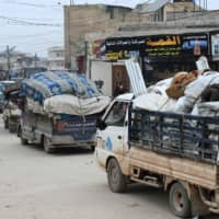 Syrians drive with their belongings as they flee the town of Atme in Syria's northwestern Idlib province near the Turkish border Wednesday, following a weeks-long regime offensive against the country's last major rebel bastion. | AFP-JIJI