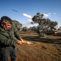 A Syrian rebel fighter remotely fires a rocket from a truck-mounted launcher at a position in the countryside of Idlib toward regime forces positions in the southern countryside of Syria's Aleppo province on Monday. | AFP-JIJI