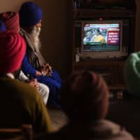 Farmers watch a broadcast of India's Finance Minister Nirmala Sitharaman presenting the 2020 budget, at a village on the outskirts of Amritsar on Saturday. | AFP-JIJI