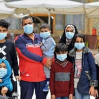 Members of an Iraqi Shiite family, all wearing masks, pose for a picture during their visit Tuesday to the shrine of Imam Ali in the holy Iraqi central city of Najaf, where the first case of coronavirus COVID-19 has been documented in Iraq. | AFP-JIJI
