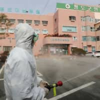 A South Korean health official sprays disinfectant in front of a hospital where 16 infections have now been identified with COVID-19 in Cheongdo County near Daegu on Friday. | AFP-JIJI