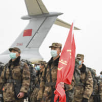 Chinese military medical staff stand in formation after arriving at Wuhan Tianhe International Airport in Wuhan in central China's Hubei Province Sunday. | CHENG MIN / XINHUA / VIA AP
