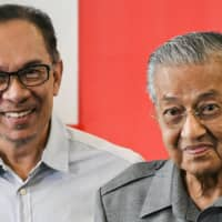 Malaysia's Prime Minister Mahathir Mohamad (right) and his one-time ally Anwar Ibrahim leave a news conference in Kuala Lumpur in June 2018. Mahathir kicked off a leadership race after he abruptly submitted his resignation to the king on Monday. | AFP-JIJI