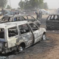 Vehicles gutted by suspected members of the Islamic State West Africa Province (ISWAP) during an attack on late Sunday are seen Monday in Auno, Nigeria. Jihadists killed at least 30 people and abducted women and children in the raid. | AFP-JIJI